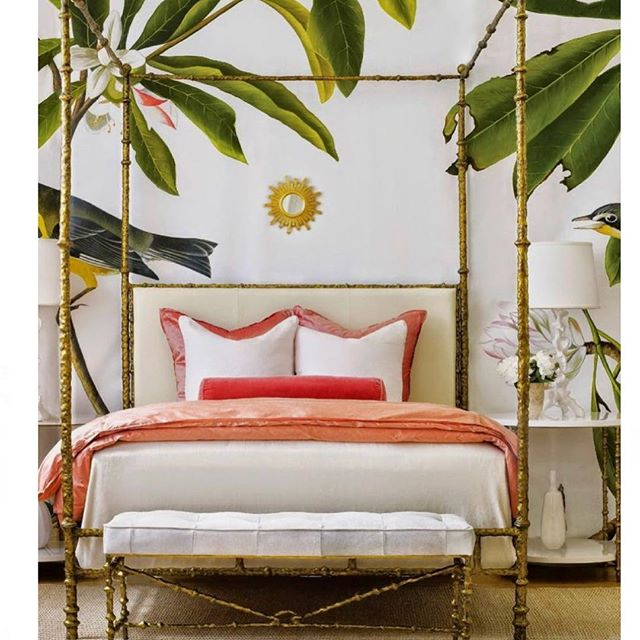 A tropical-themed bedroom with a gold bed frame, white and pink bedding and palm leaves over head