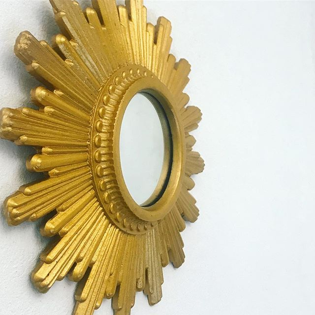 A sun-shaped golden mirror hanging on a while wall