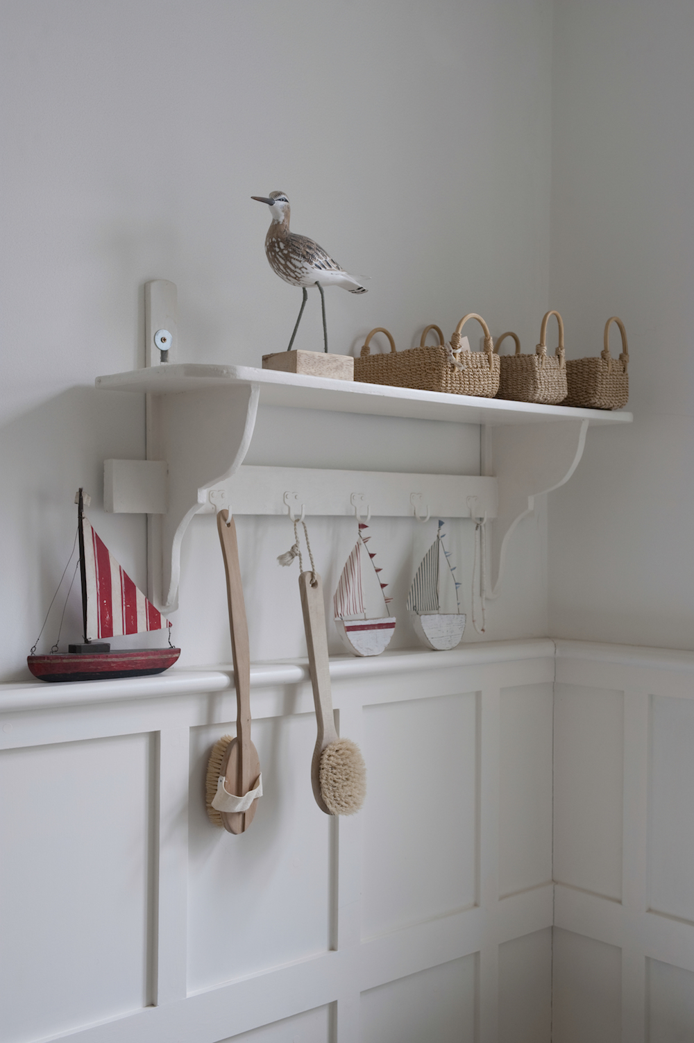 Holiday Home Inspired: A white shelf with wicker baskets, a bird ornament and wooden boat ornaments around it