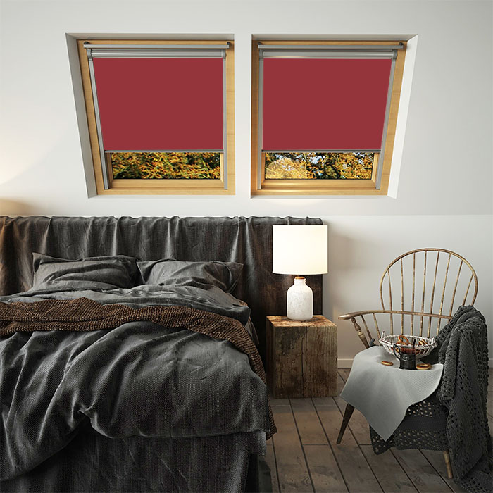 A pair of deep red skylight blinds for velux windows in a bedroom
