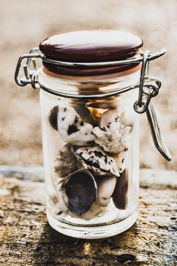 A glass jar filled with seashells and rocks