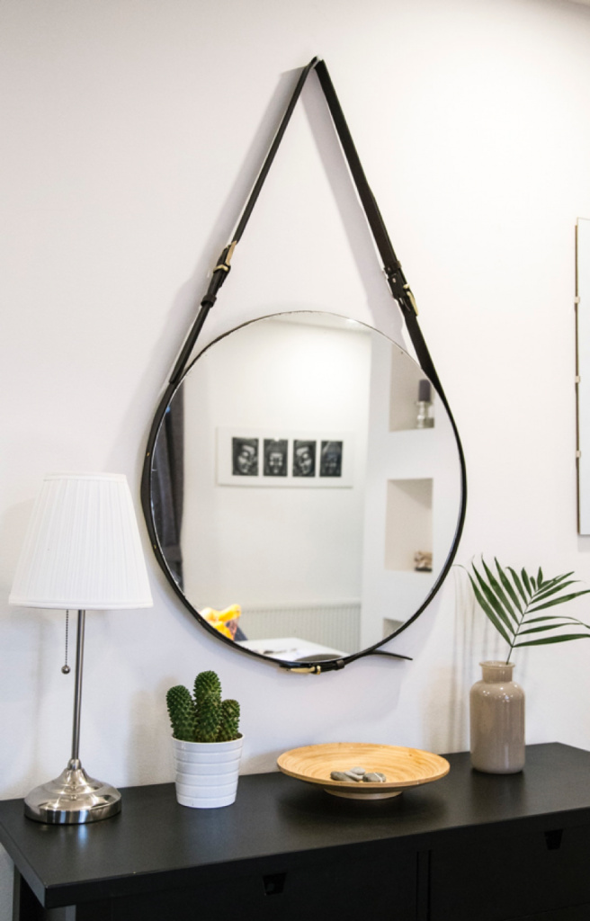 A round mirror hanging on a white wall above a black sideboard