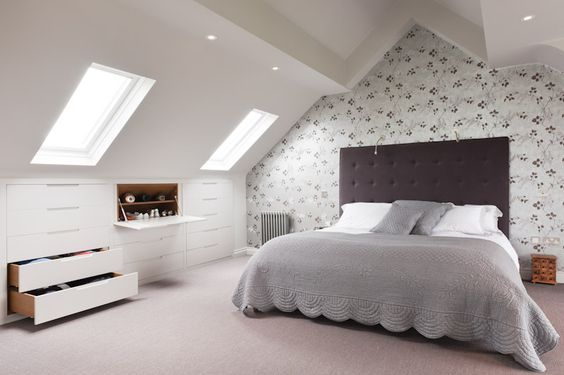 An image of a light and contemporary bedroom in a loft conversion with skylight windows