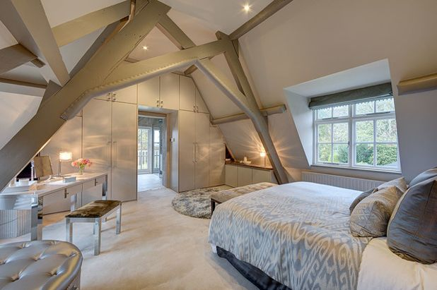 An image of a bedroom loft conversion with wooden beams