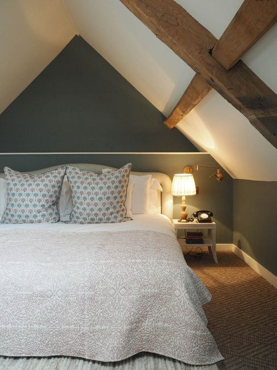 An image of a two-toned loft bedroom with wooden beams