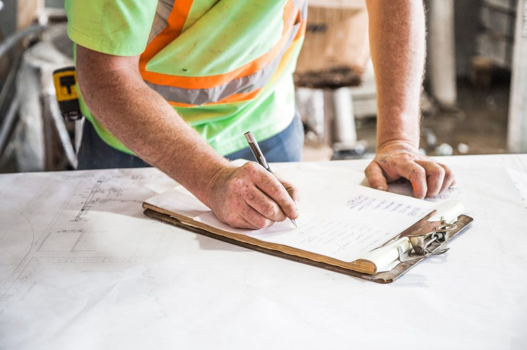 An image of a builder writing notes on a clipboard