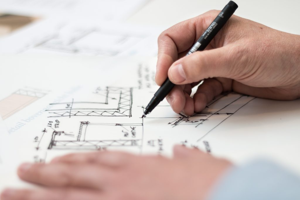 An image showing two hands sketching architect drawings on a large sheet of white paper
