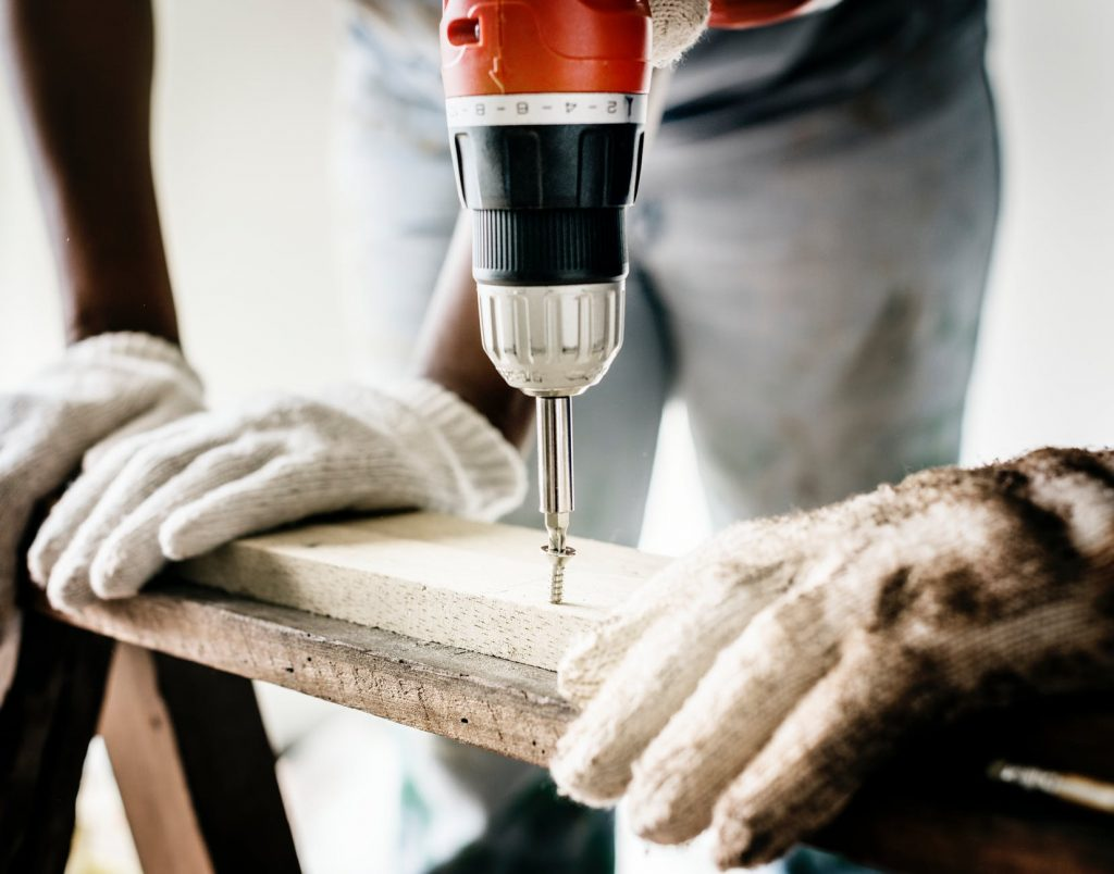 An image showing two gloved hands holding planks of wood and a drill drilling through