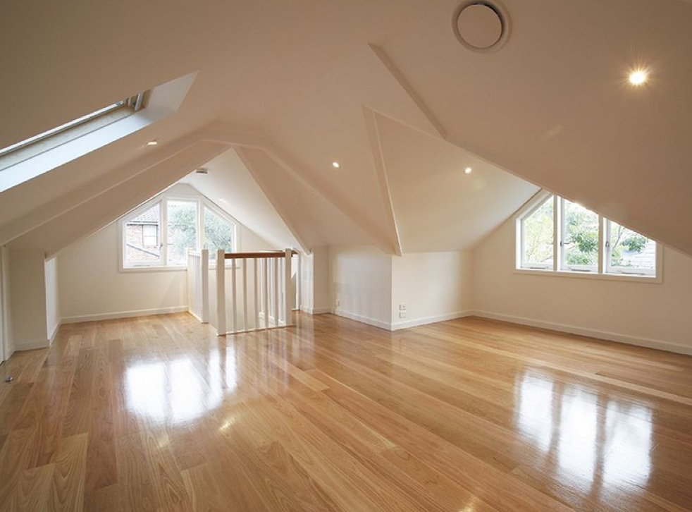 An image showing a large and well lift loft conversion space with skylight windows dotted around