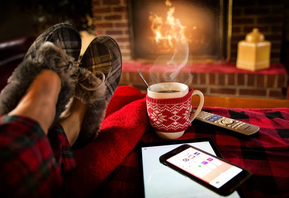 An image showing a roaring fire, hot drink and fluffy slippers