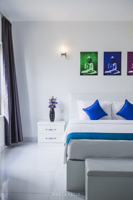 An image showing a white loft conversion bedroom with blue and green accessories.