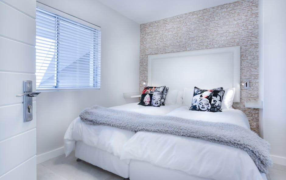 An image showing a white bedroom with neutral statement wallpaper.