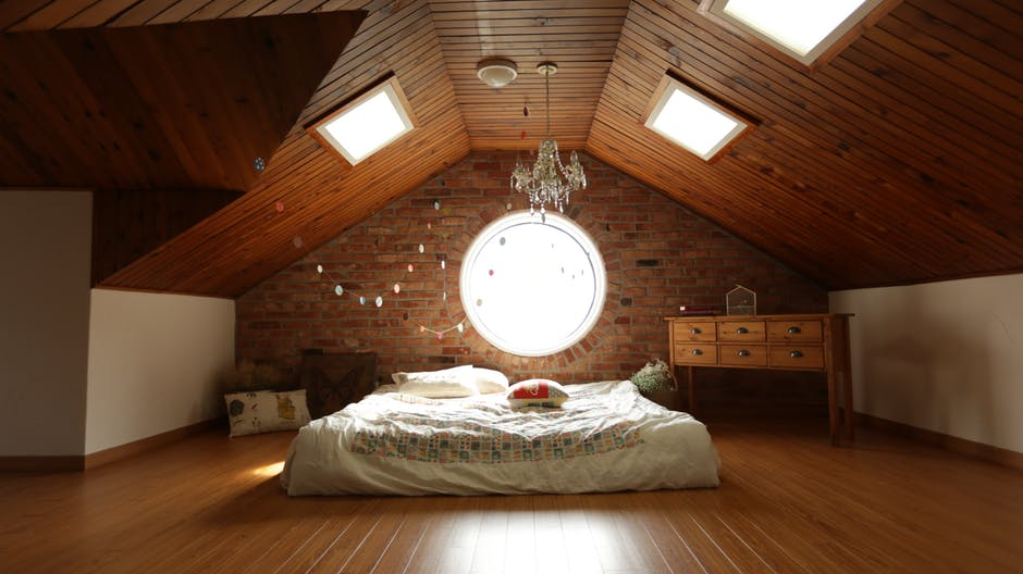 An image showing a loft conversion with a bed placed underneath four skylight windows