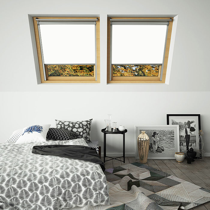 An image showing white blackout skylight VELUX compatible blinds in a bedroom