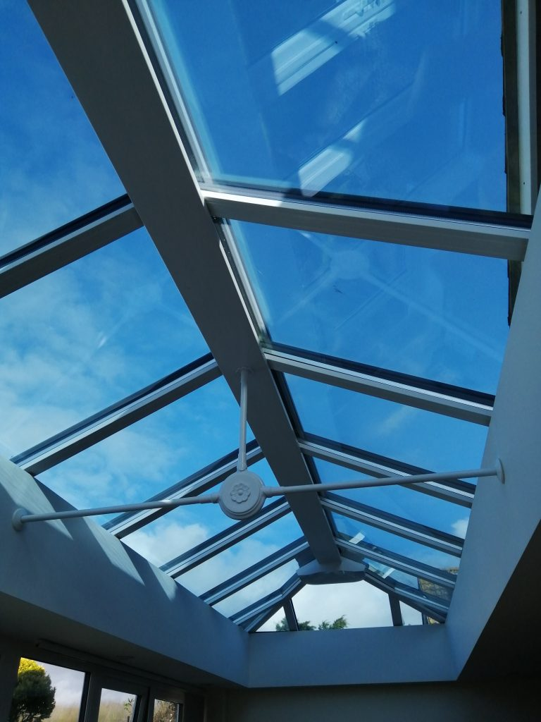Conservatory roof blind rolled back on a peaked glass roof window